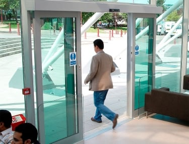 man walking through automatic sliding door with green glass